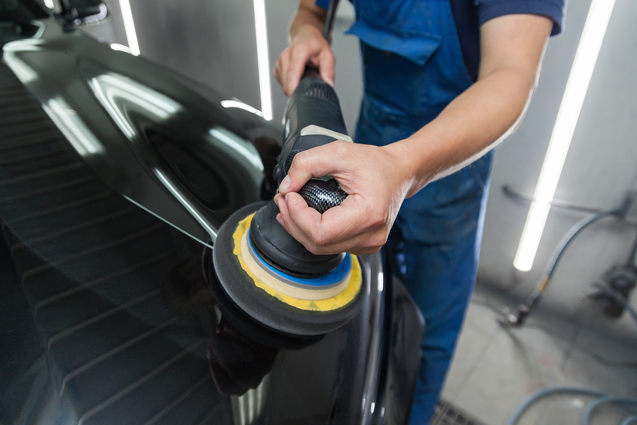 polisher polishes the body of the vehicle with special wax to protect the car from minor scratches and damage, using a polishing eccentric machine to cover black hood after washing.